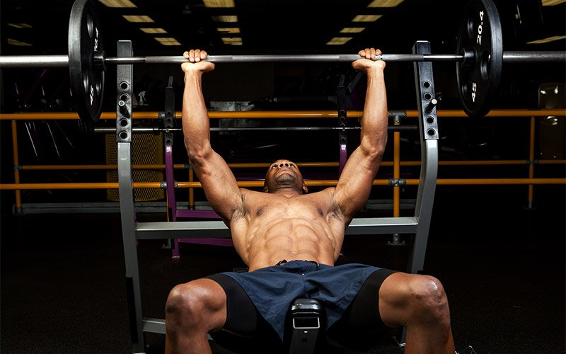 Man in navy shorts performing barbell incline bench press