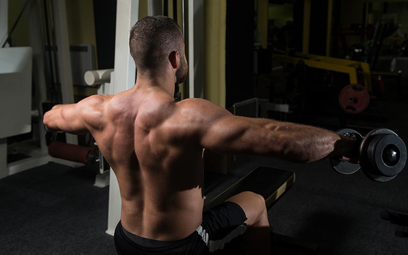Athletic Man Using Dumbbells for Lateral Raises