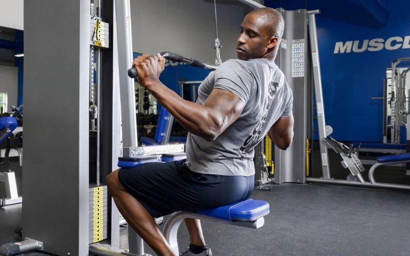 Спортивный (ый) мужчина делает тяги верхом в спортзале