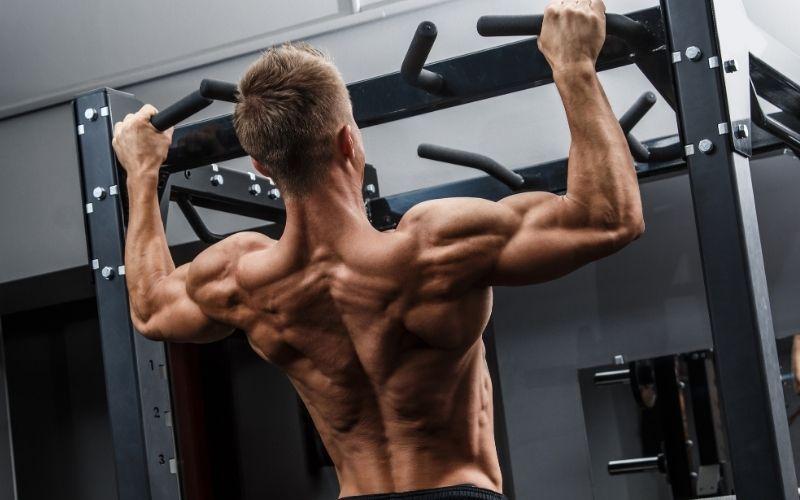 Мускулистый мужчина, выполняющий подтягивания в тренажерном зале